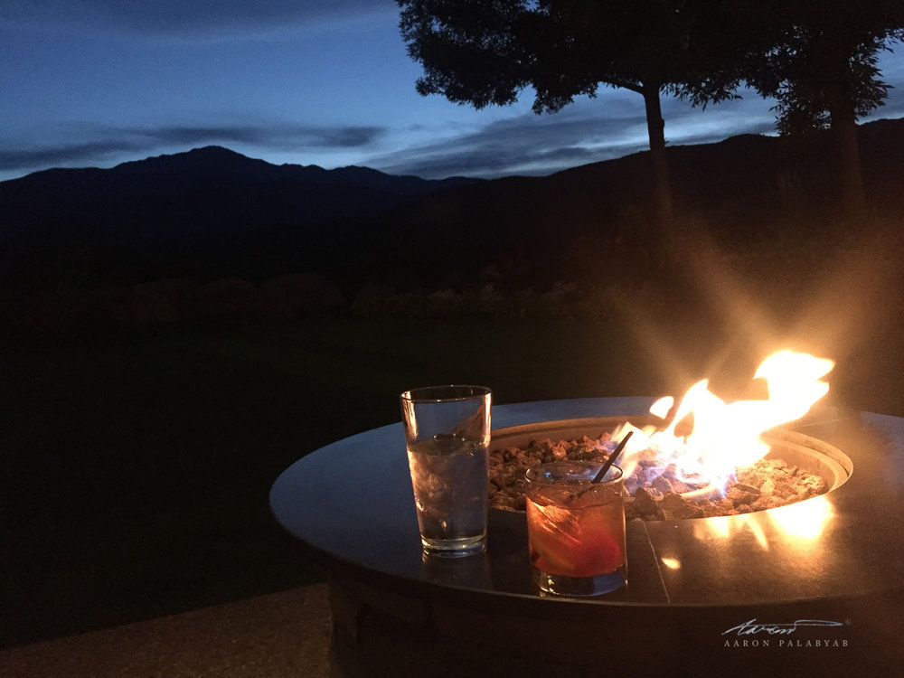 Cold cocktail, warm fire, and the Rocky Mountains at twilight