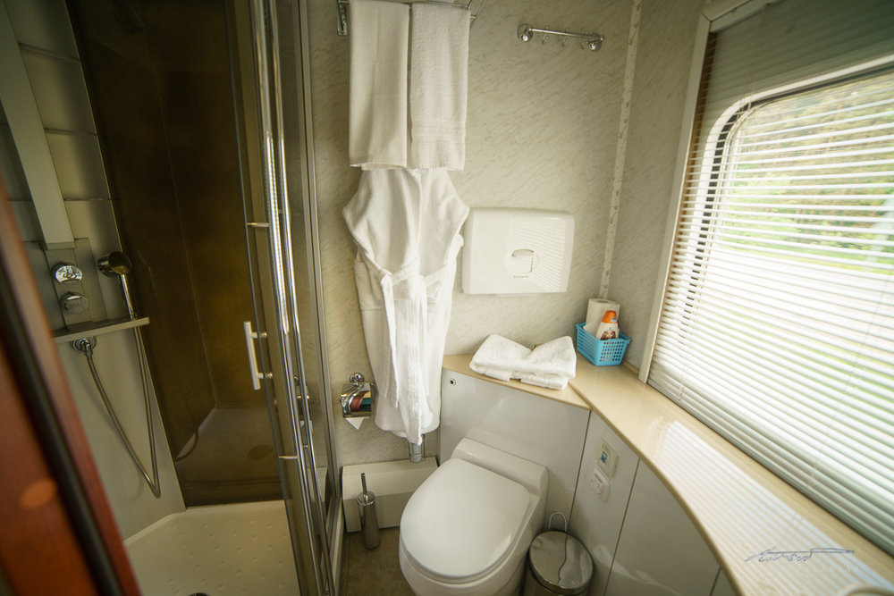 The ensuite bathroom, complete with bathrobes, full-size toiletries, amenity kits, and a heated floor