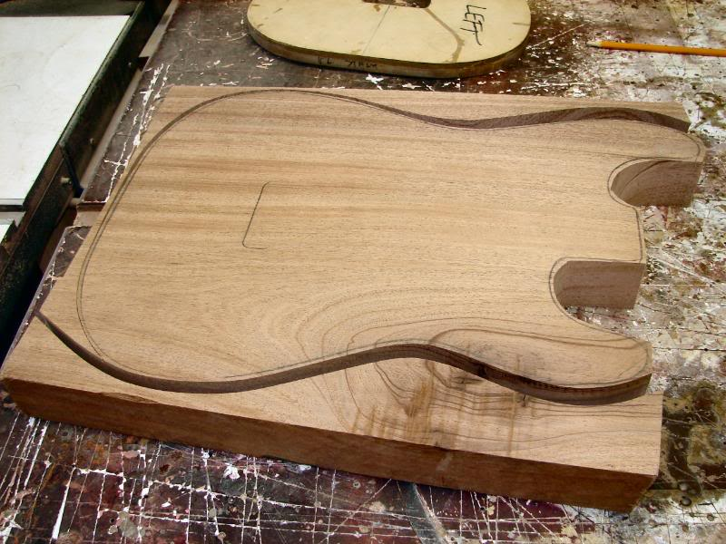 A one piece Mahogany, and well dressed strat. I have taken a 13 ½ inch wide section of Mahogany. Planed it to the approximate thickness, of 1  7/8 then using the panel sander to take it down to almost 1 ¾. Use the template to trace out the rough shape and bandsaw, or jig saw a basic blank.
