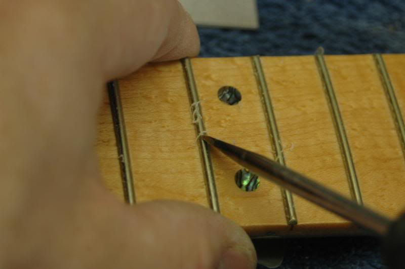 "Once the majority is removed, I go back gently scraping each edge of the fret. I don't have to be NASA clean room certified here, the fret leveling, and polishing will remove the remaining residue. Some will not remove the lacquer at all, but allow the fret leveling to ""clean"" the fret. I do not, because I feel that allows the lacquer to remain far too high up the edge of the fret. It will eventually separate, chip, and look rather messy."