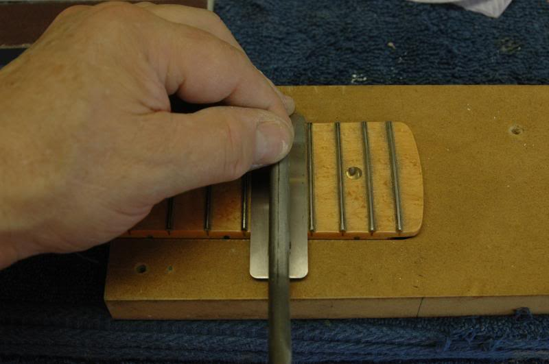 If you're good, or crazy, I'm not sure.. you can do it like in the previous photo, risking scratching the fingerboard, or you can use a protector, as seen here.