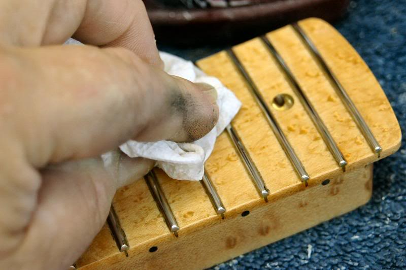 I do the same on the heel, then re mask and do the edge of the heel. Once that's done I begin polishing the frets, I use several methods, depending on the neck, here I'm going over each with a cleaner car wax. It's perfect because it will polish the fret and clean any residue from the base of the fret.