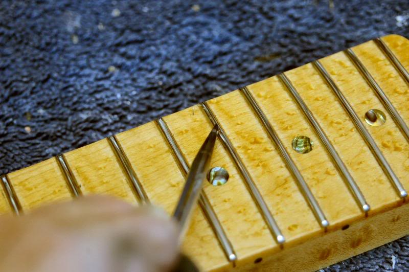 After the frets are polished, I'll examine each closely and, using my scraper, remove any lacquer, that I may have missed. Then re-polish those frets.