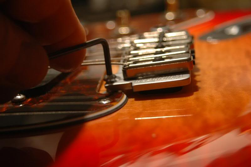 "The Wilkinson Tremolo has a setscrew in the bottom of the post, used to lock it securely, improving transmission of the string vibrations into the body. You must loosen them, then lower the posts until the bridge looks about right. I check the back ""lines"" to be certain the body of the tremolo is parallel to the guitar's surface. Now I check the strings height around the 20th fret to see that there is clearance to work with."