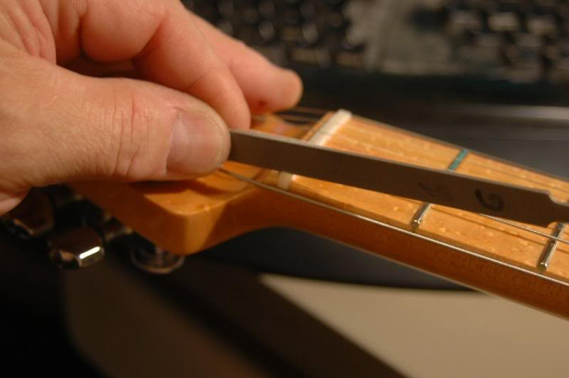 "If you recall, as I was doing the assembly, I pre-slotted the nut with an approximate depth of slot, I now finish that aspect. I lift each string from the slot, give it a few swipes with the nut file, and reseat the string. I check each one leaving about 1/64th at the first fret under the first string and about 3/128ths under the 6th. Unplugged, I pluck each string, you will be able to hear if there is any fret buzz, or the dreaded ""citar"" sound."