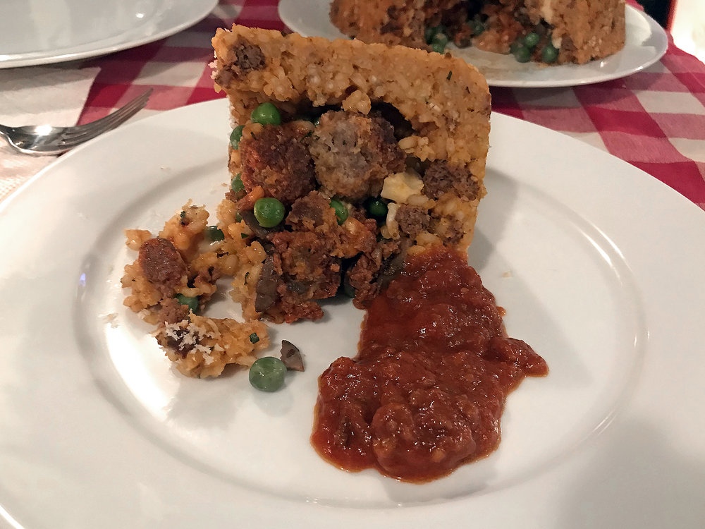 A slice of timbale with some ragu on the side