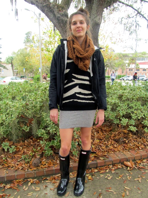 University of Florida Student, Alexa Asendorf wears a zebra print sweater under a dark navy parka jacket and over a short gray skirt. She accessorizes the look with a pair of black rubber hunter boots and a large brown ruffle scarf