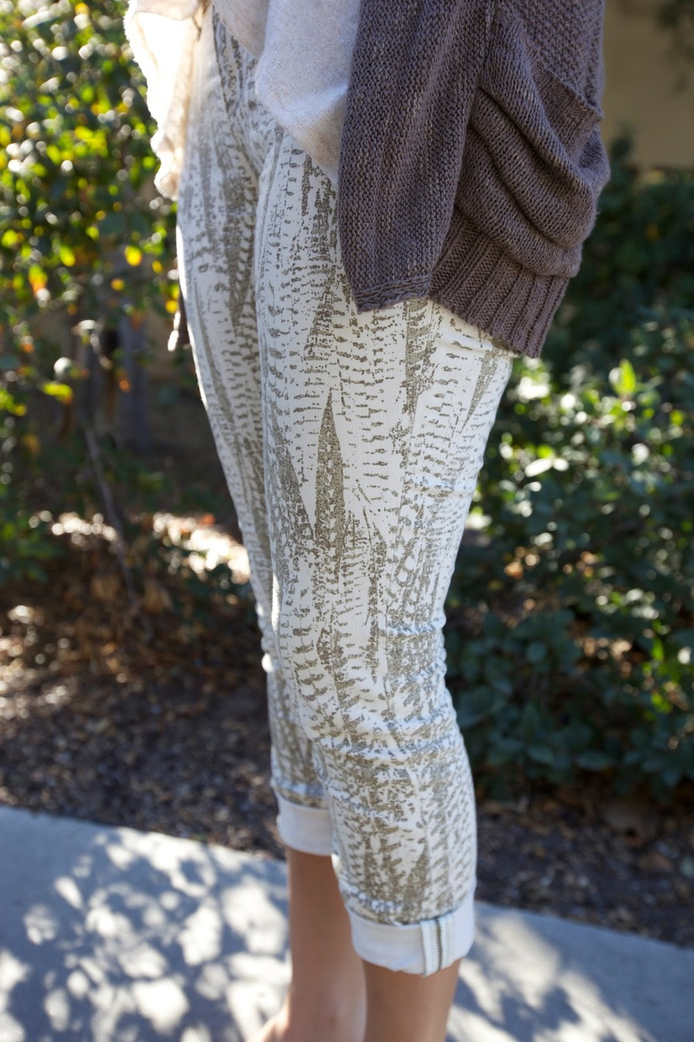 Miruna, a Santa Clara University student wears a stone gray cardigan over a ruffle white scoop top and leaf nature print white and sand leggins