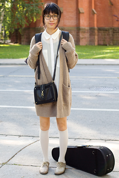 University of toronto student walks to her violin music class wearing a beige maroon oversized buttonless cardigan over a white shirt and paired with knee length white socks and ash gray suede laced shoes