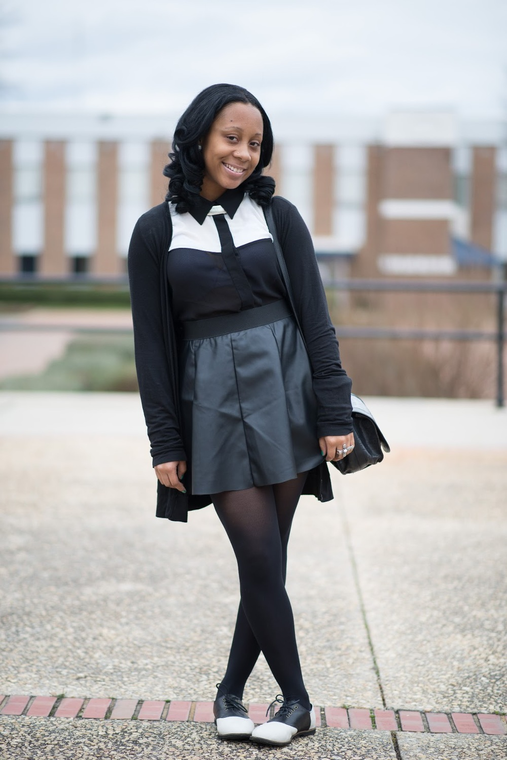 Deshaune is a student at St. Augustine's University in Raleigh, NC. She's wearing a monochromatic outfit. Black Cardigan, contrast white and black shirt over a high waist black skirt, a black leather bag and black and white saddle shoes