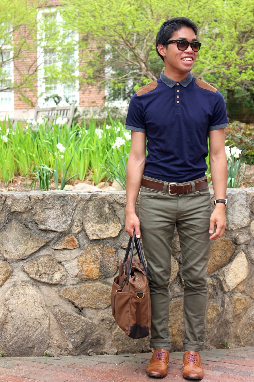 Josh K, UNC student and blogger featured wearing olive jeans, brown brogues with pink laces and a blue buttoned up brown contrast shoulder polo. He accessorizes them with a brown bag