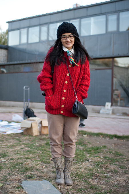 Beijing University student wears a red chunky cable knit sweater over khaki pants and khaki desert boots. Accessorized with a black knit hat, a colorful cravat inspired scarf and a black shoulder purse. 北京工业大学的在校生在卡其裤卡其色沙漠靴矮矮胖胖的电缆穿的是红色的针织衫。装饰与黑色针织帽,五颜六色的围脖风格的围巾和肩膀上的一个黑色的钱包里。
