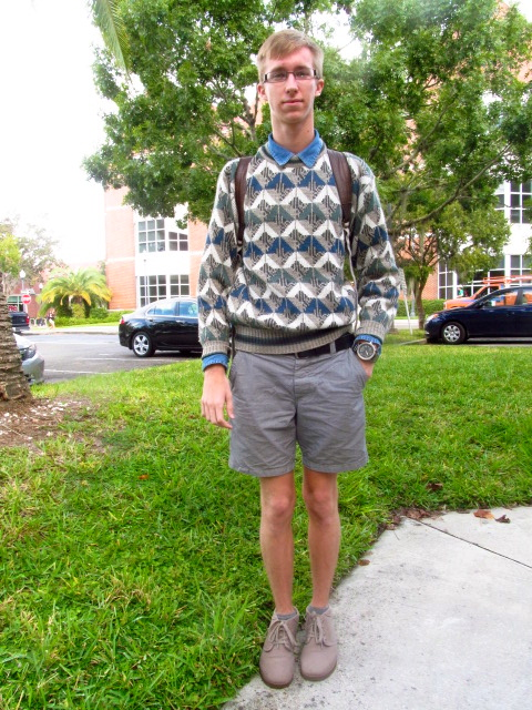 UF student Brett wears a geometric pattern sweater for men over a blue denim shirt and grey chino shorts