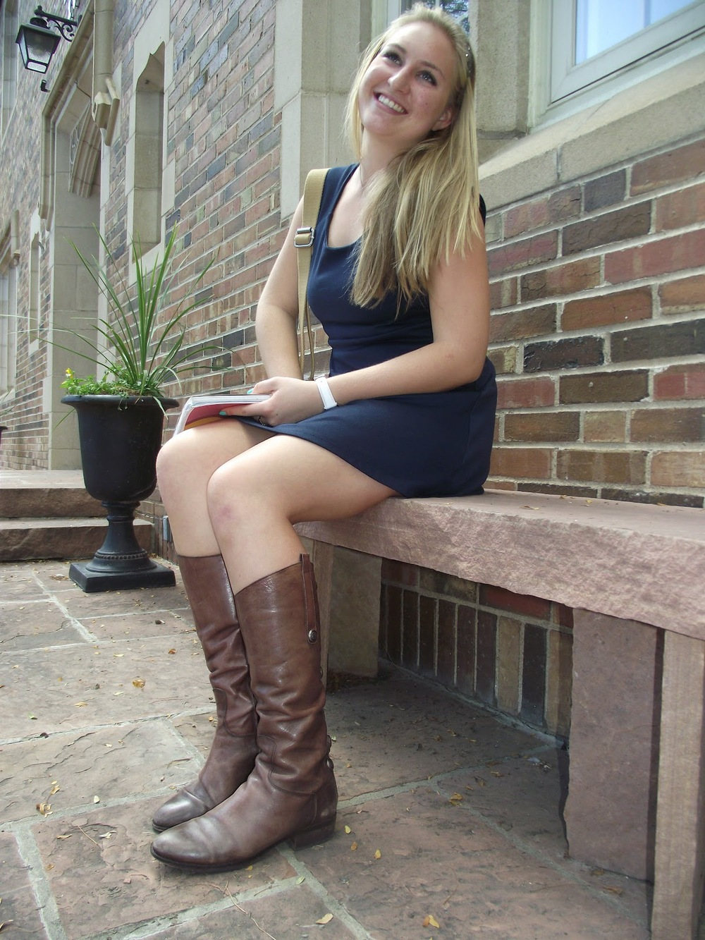 Kacey Paulin, CU Boulder Student wearing a blue dress and multicoloured patch bag with brown boots.