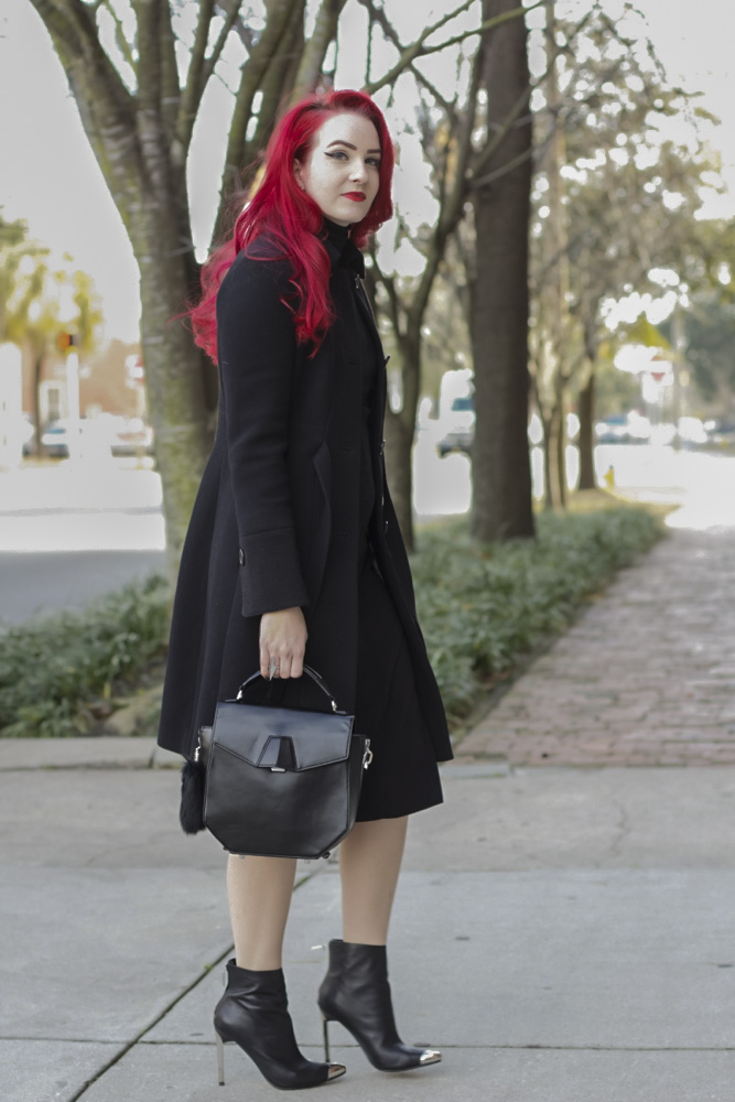 Sarah, a bright red haired SCAD student from Savannah, Georgia wears a dark black peacoat over a  black winter dress and pairs them with a black leather bag with a fur tail accessory and silver toed and heeled black stilettos.