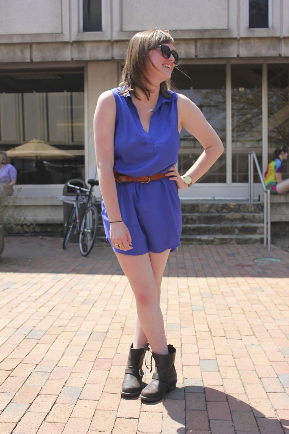 UNC Junior, Nan C. wears a blue sleeveless dress cinched by a brown belt golden buckle and a pair of leather round buckle boots. Also wears a North Carolina state shaped necklace