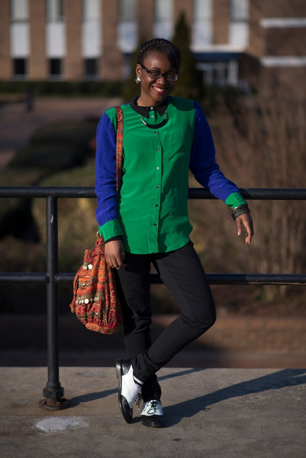 Kisha a St. Augustine's University Student is wearing a gorgeaous contrasting black collar green body and cuffs and blue sleeves shirt. She also wears black slim jeans and a pair of black and white brogue derby spectators and an aztec or native american print backpack