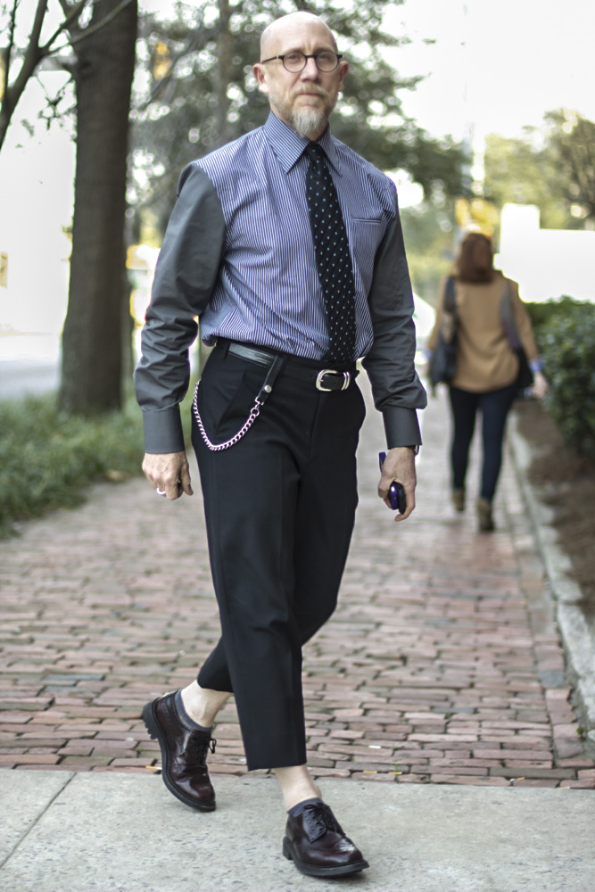 Michael Fink is the dean of the Fashion school at SCAD where he is often seen around campus wearing Japanese fashion label Comme des Garçons. In this photo he wears a contrasting gray sleeves and striped blue body shirt with a blue polka dotted tie tucked into a pair of high waisted high cuffed black trousers pants paired with dark brown or black brogues and gray ankle socks. He is also sporting a pair of harry potter round glasses.