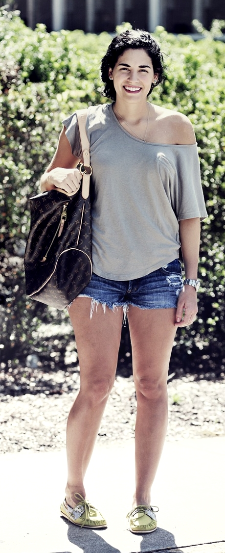 SCAD student wears an asymmetrical grey top over blue jean jorts and accessorizes her outfit with a Louis Vuitton shoulder bag and yellow boat shoes.