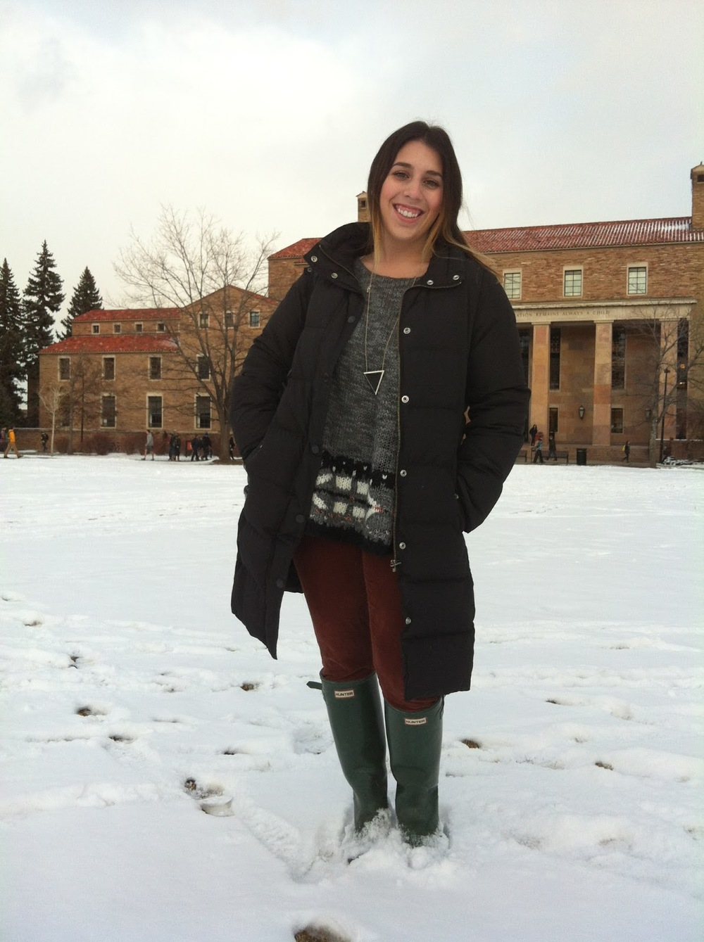 Molli Vita,  University of Colorado at Boulder student wears a J.Crew Puffer Jacket gray pattern Free People sweater over a pair of brick maroon Lauren Conrad for Kohls corduroys tucked into green Hunter Rain rain and snow boots. She is also wearing an interesting golden chain with a black obsidian triangle Luna B necklace / pendant