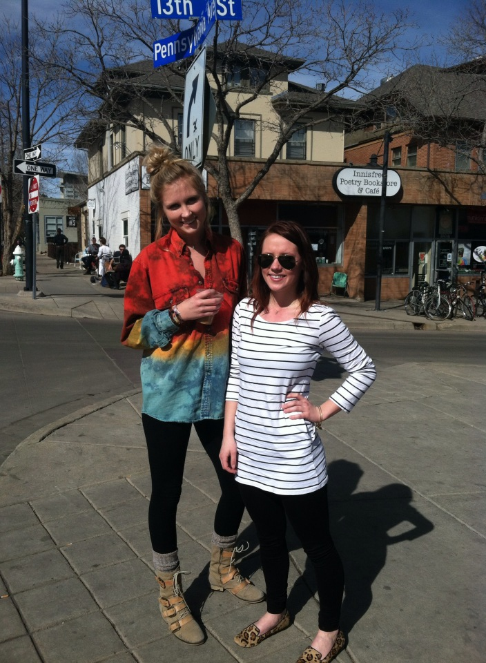 These two CU Boulder students are embracing early spring. On the left we have a tri-color red yellow teal tie-dye denim shirt over black leggings tucked into high-top tan boots. On the right we have a long nautical striped long sleeved shirt over black leggings and leopard print slippers.