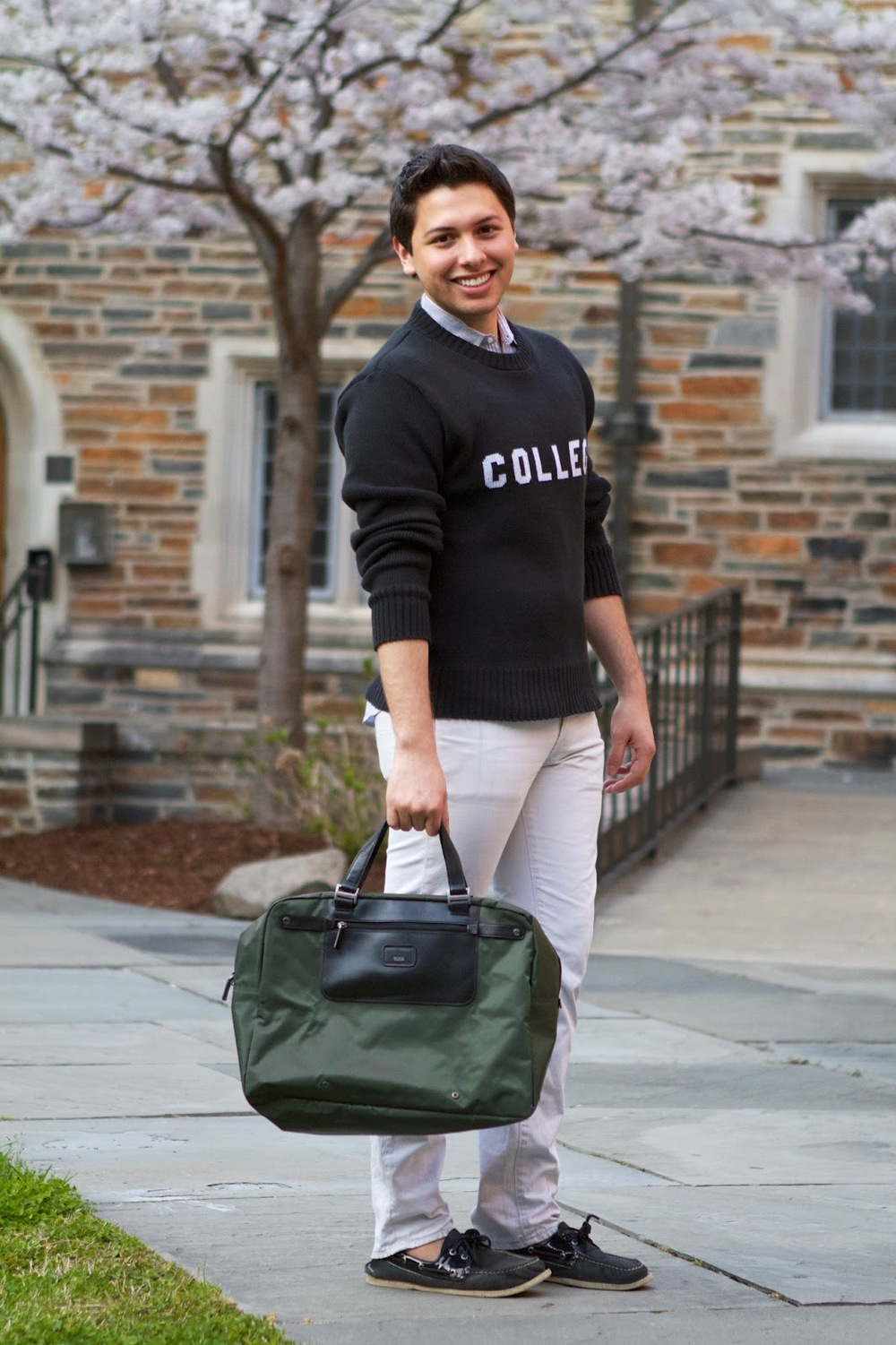 Chris Hurtado is a Duke sophomore wearing the School House Bluto Blutarsky sweater over a blue oxford cloth button down shirt OCBD, white slim jeans, gray and black contrasting boat shoes and a hunter green and black leather trim handbag