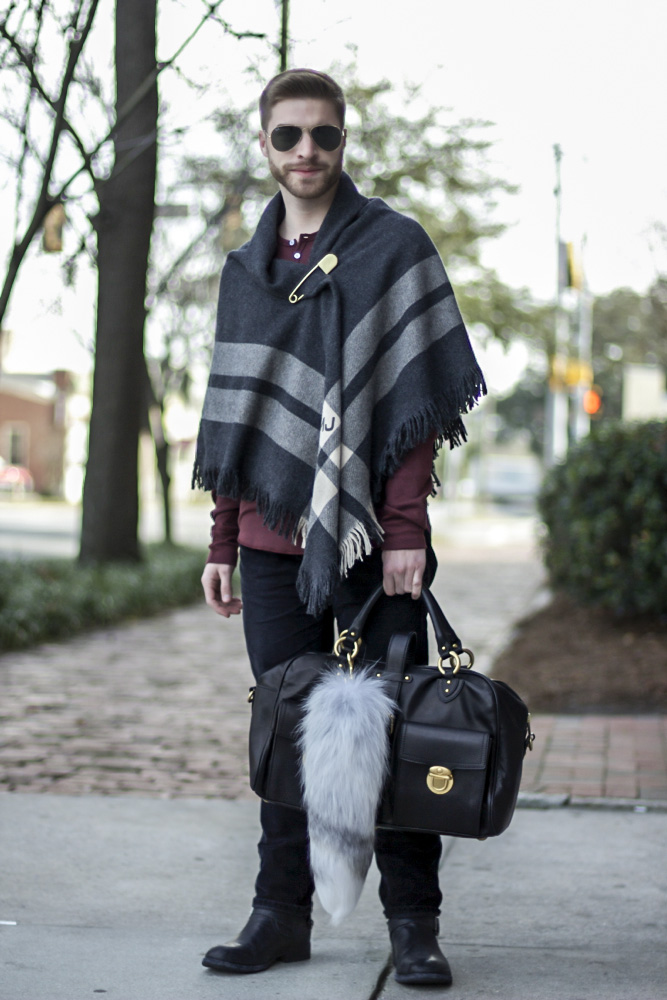 SCAD student David keeps warm by wrapping himself in a striped two-tone gray and white scarf, pinned down by an over-sized silver safety pin. He wears it over a burgundy henley, slim black jeans and black leather boots. He accessorizes his look with a golden and black leather bag that has a furrtail attached to it.