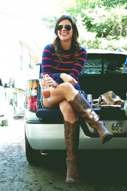 University of Kansas Jayhawk student wears a striped blue and orange crewneck sweater with jean shorts and brown cowboy boots for tailgate