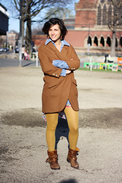 Harvard student wears an oversized brown blazer as a coat over a blue denim shirt and a side mullet pattern summer dress paired with a matching orange rust pair of leggings and brown boots.