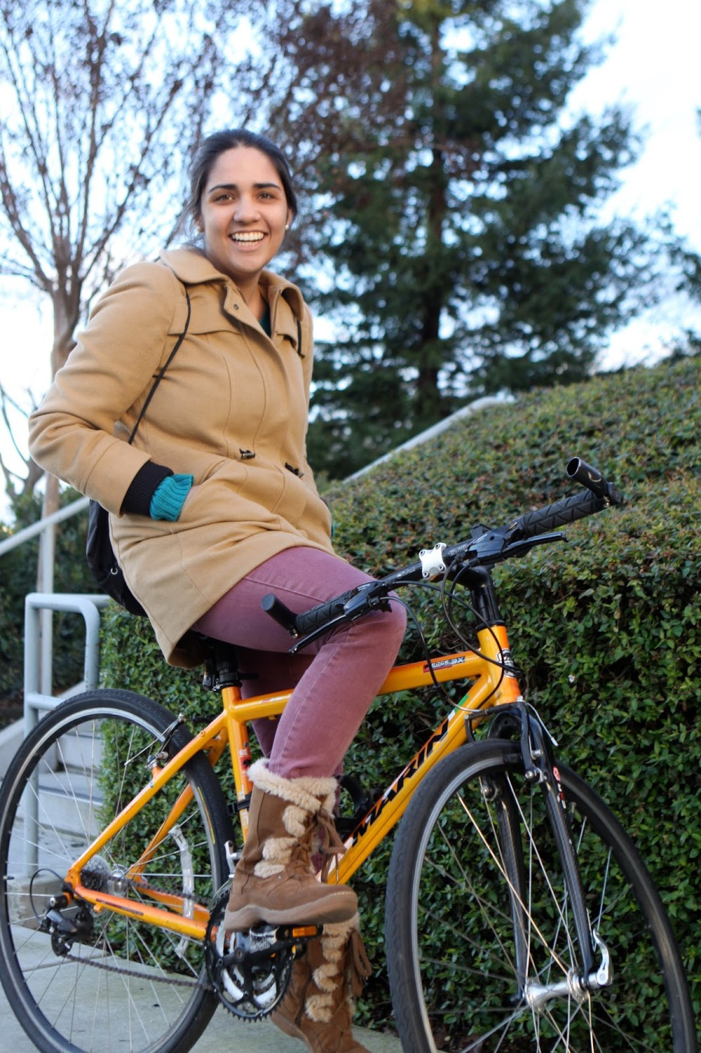 Katya, a Santa Clara University student wears light purple mauve jeans and a tan peacoat with fur-trimmed winter boots while she rides her bike.