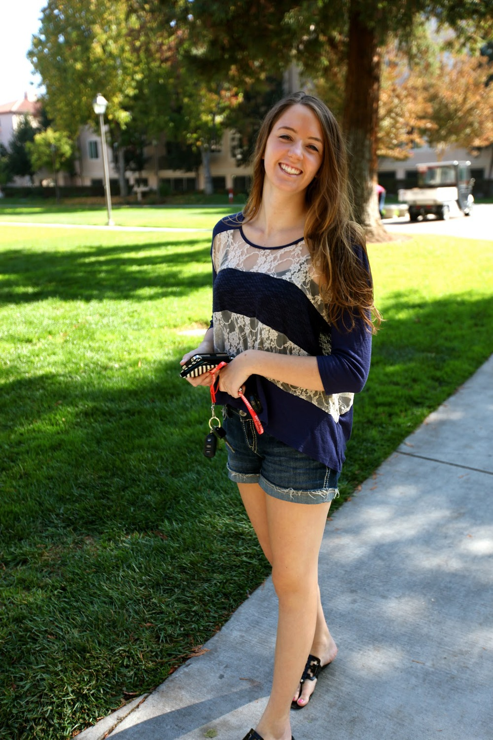 Amy Grills, Santa Clara University student wears a mixed fabric top made of lace and blue solid pieces with jean shorts jorts and black sandals