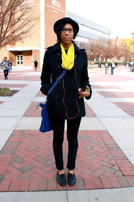 Virginia Commonwealth University Student wears a black double breasted pea coat with skinny black jeans and black ribbed braided leather loafers. She accessorizes them with a  black fedora, a yellow infinity scarf and a blue shoulder bag.