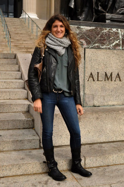 Columbia University in New York City alumni Mila wears a dark chocolate brown leather jacket over a gray moss round button shirt and pairs that with a pair of skinny blue jeans high leather boots and a gray infinity scarf