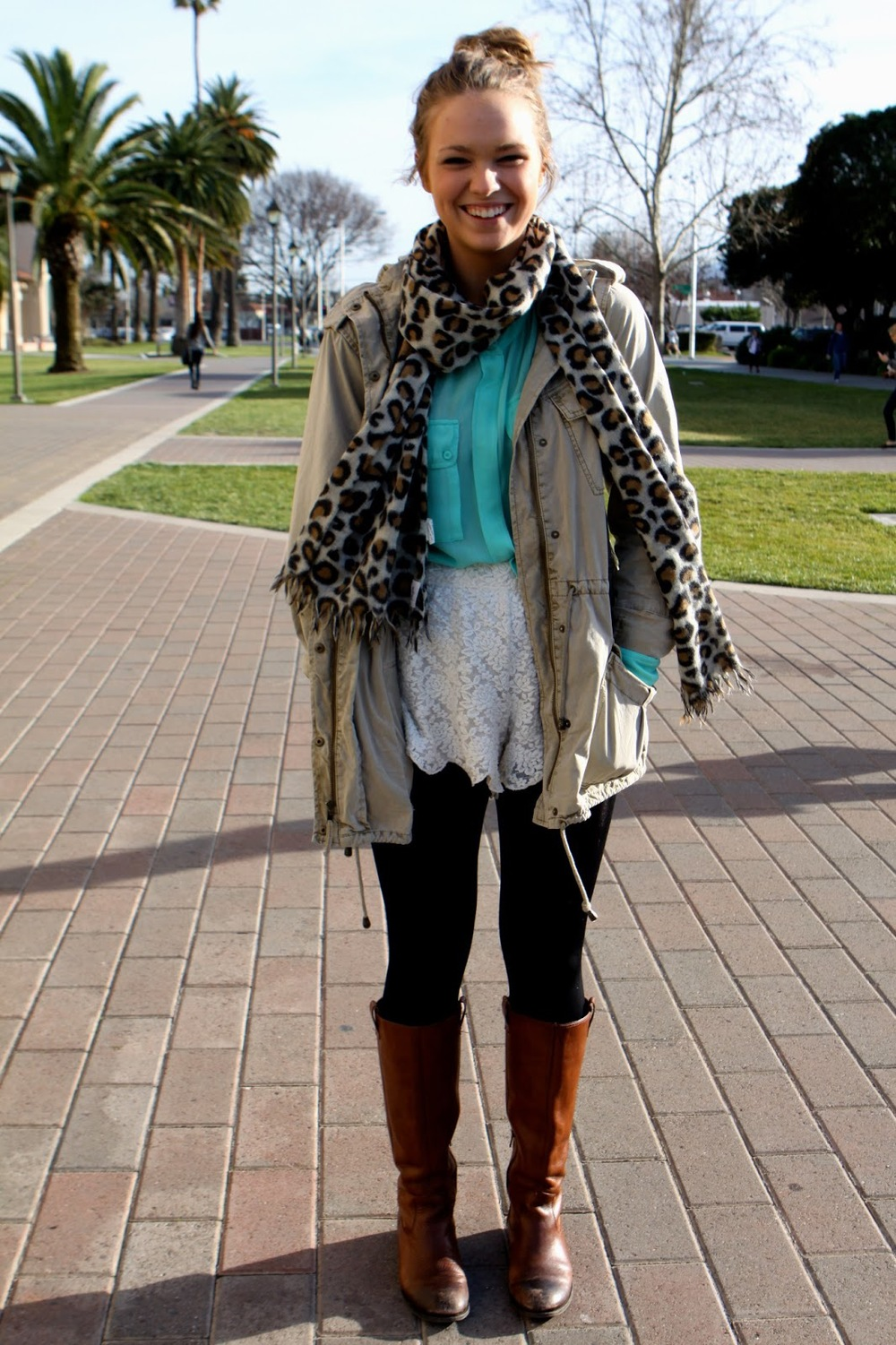 Carly, a Santa Clara University student wears a leopard print scarf and a khaki jacket over a teal loose shirt, a cream white lace skirt, black leggings and high brown boots.