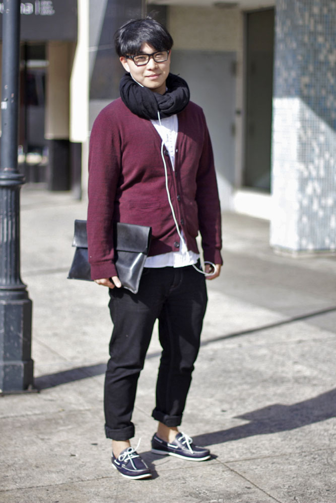 Savannah College of Arts and Design SCAD student wears a black infinity scarf with a burgundy cardigan over a white shirt and black rolled up skinny jeans, blue boat shoes and carrying a dark dossier document carrier.