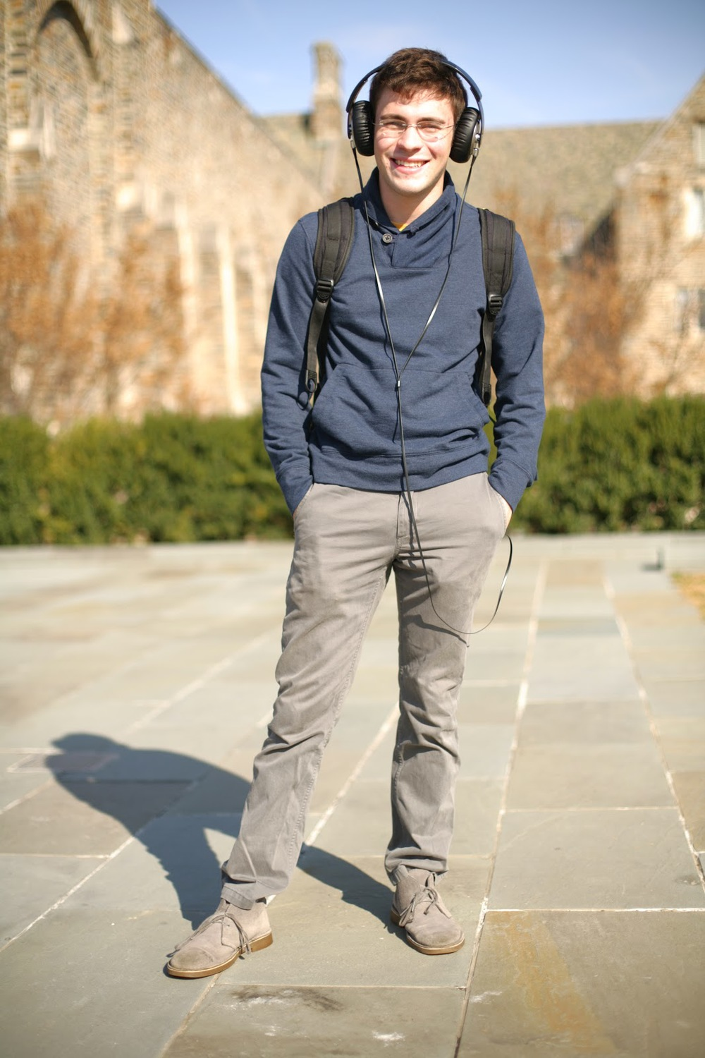 Duke University Sophomore Eugene Rabinovich sports a huge pair of black headphones over a grey and blue ensemble consisting of a buttoned shawl collar sweater, grey chinos and grey suede chukka desert boots.