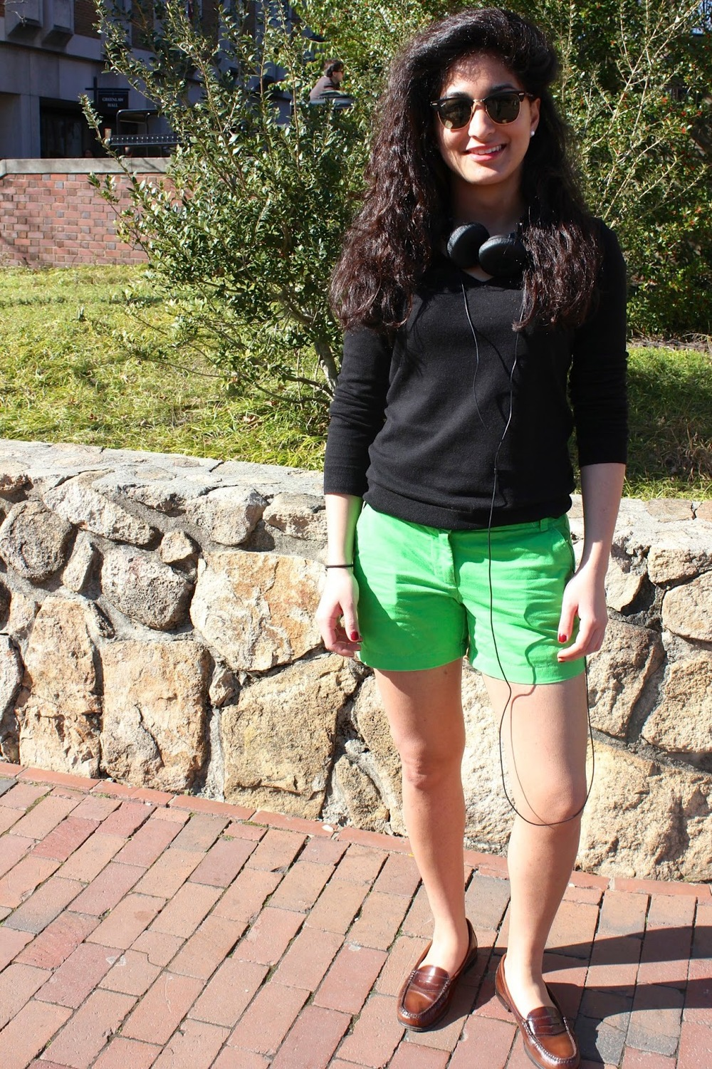 Nayab a UNC Chapel Hill student wears a simple long-sleeved black sweater over pair of lime green shorts and a pair of brown preppy penny loafers on campus.