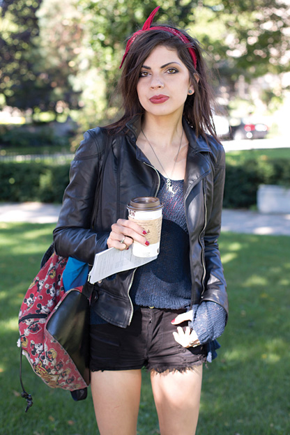 University of Toronto student showcases a rockabilly hipster look combining a leather jacket with a knit top, skinny black jean shorts and a mickey mouse backpack