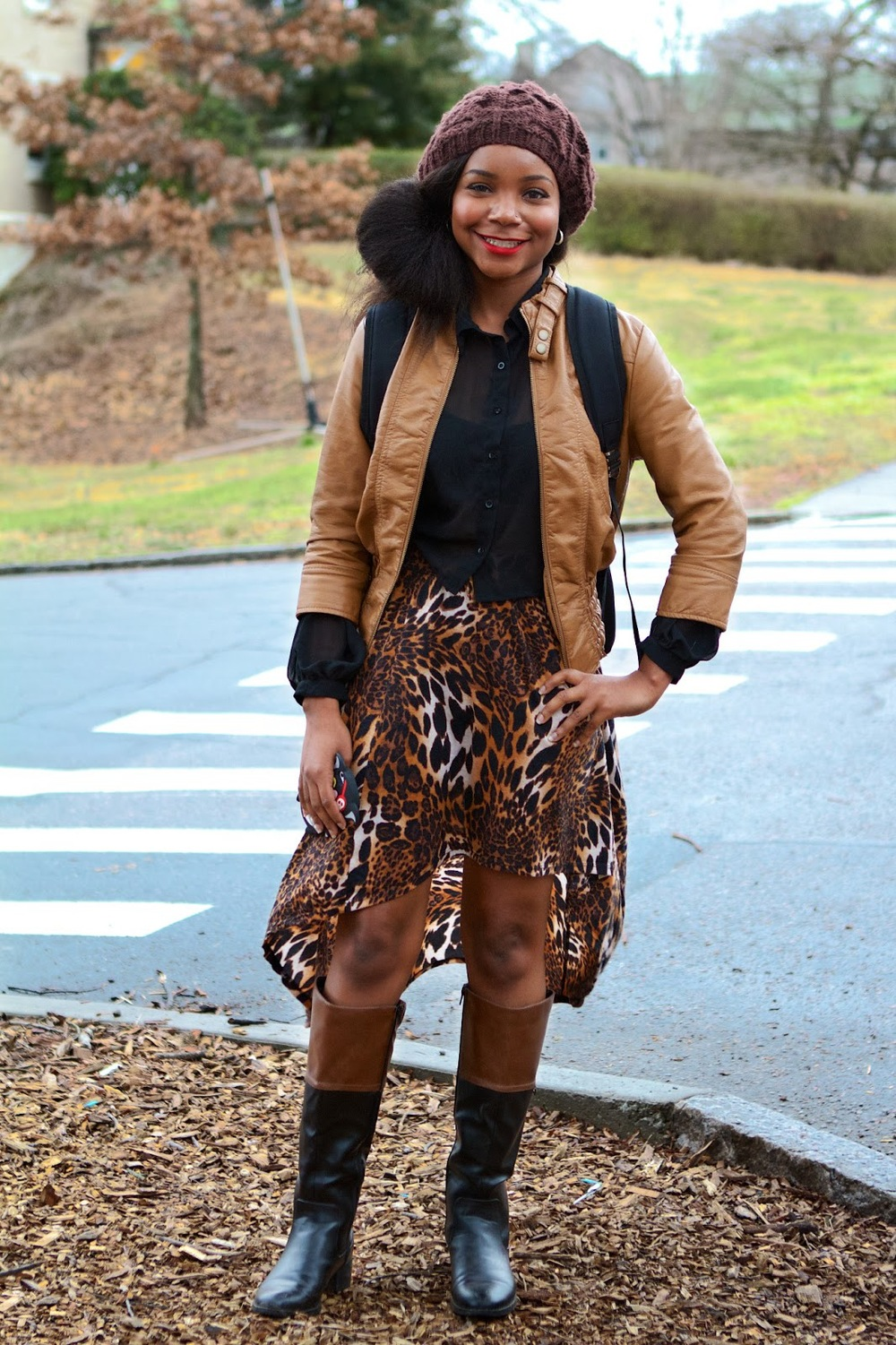 Ieshia Smith, a Duke University Junior wears a tan brown leather jacket over a see-through black shirt and a tiger print mullet dress. She accessorizes her look with a brown knit beanie, two tone brown leather boots and a blue and brown canvas leather trim backpack.