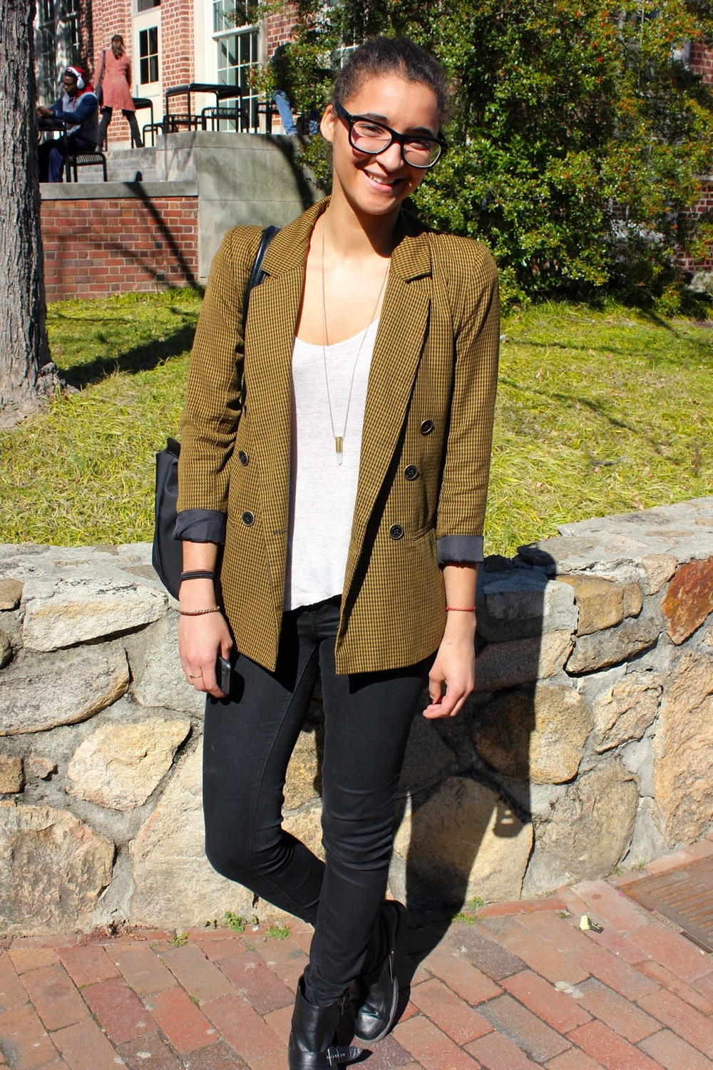 University of North Carolina in Chapel Hill student wears a vintage black and yellow houndstooth tweed blazer sleeves rolled up over a simple white scoop neck tee slim black jeans and black leather combat boots.