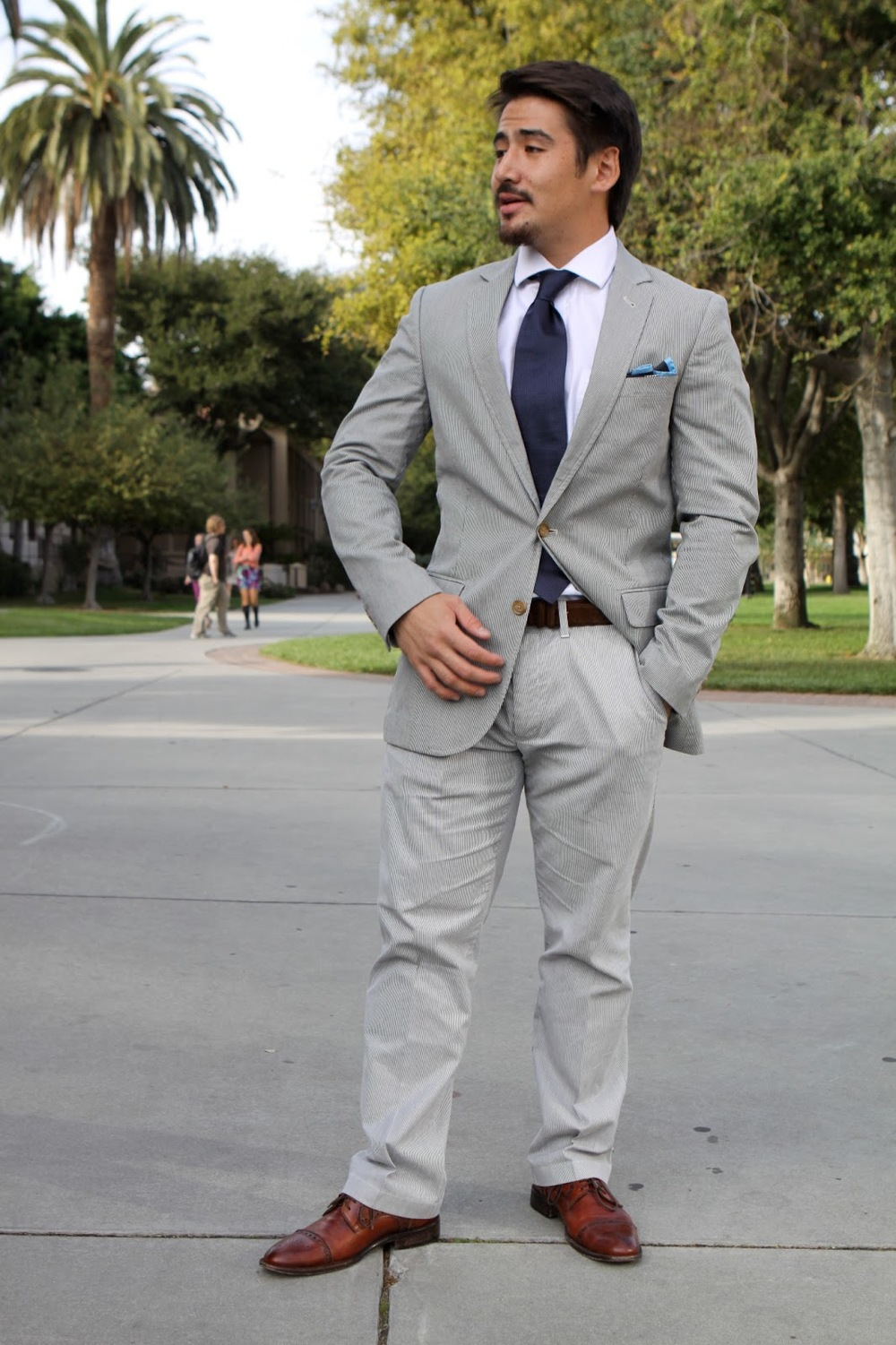 Matt, Santa Clara University student wears a blue white seersucker suit paired with a spread collar shirt, a microprint blue tie and a pair of brown brogue oxfords