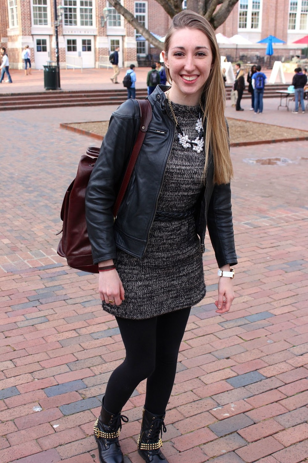 UNC Student Courtney wears a black and white interwoven dress under a black leather jacket and a clustered pearl necklace over black tights and golden studded black boots.