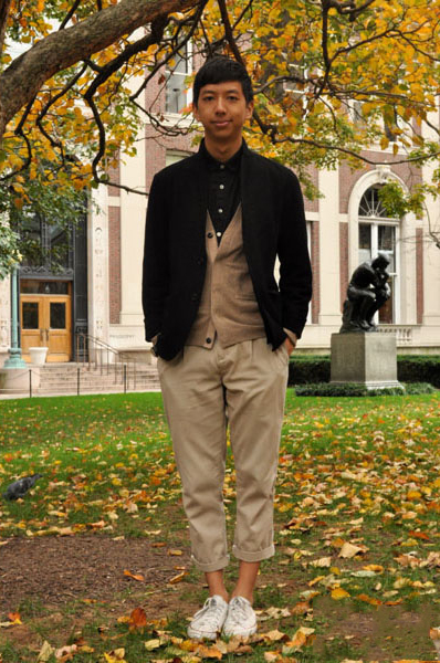 Columbia University Ethan Wong wears a neutral black and tan collegiate preppy outfit: black blazer, tan cardigan over a black shirt paired with cropped rolled-up tan chinos and white converse sneakers.