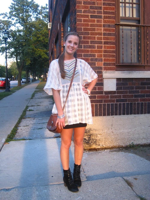Marquette University student wears a see through windowpane embroidered top over a short cropped black dress and a small brown shoulder bag and black ankle boots.