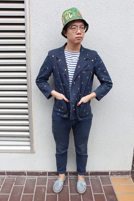 Harng, NTU School of Art, Design and Media student in singapore wears a jungle print bucket hat with a blue critter blazer and rolled up blue chinos with light teal tasseled loafers