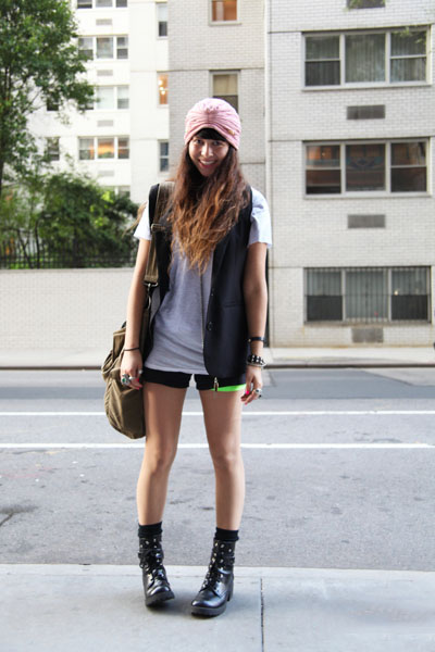 NYU student Shea Daspin wears a turban head accessory, a sleeveless blazer vest over an off white t-shirt and black short shorts and black canvas boots