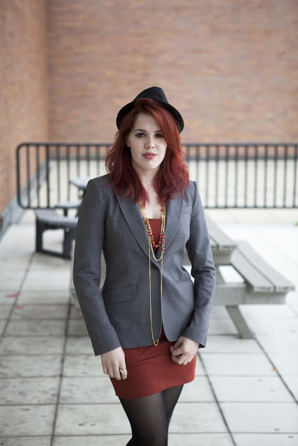 Red haired Lucy, an Advertising Photography major at the Rochester Institute of Technology RIT wears a black fedora and a grey blazer over a short cropped red dress and golden red jewelry.