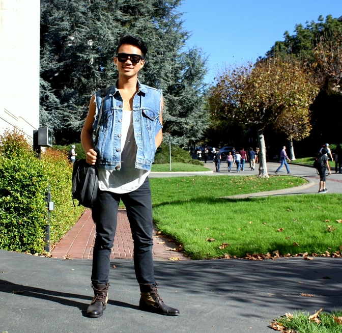 U.C. Berkeley student wears a faded jean vest over a white tank top, black gray slim jeans and brown canvas black leather boots he is carrying a black leather shoulder bag and a large furry tail accessory