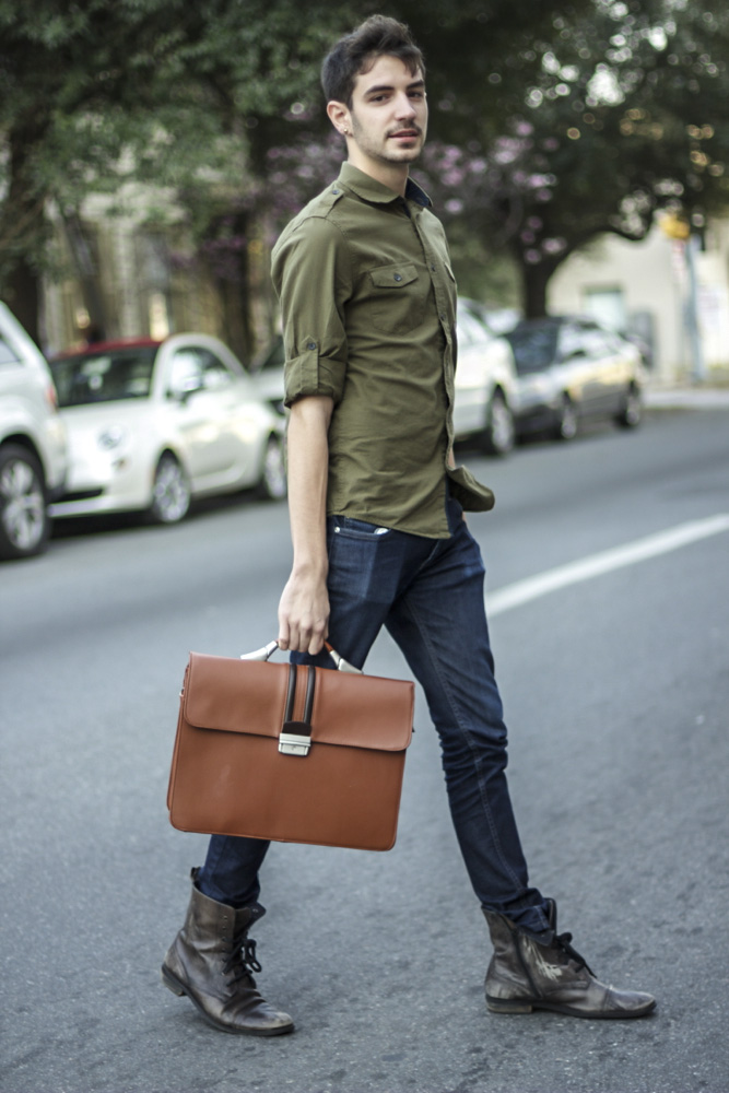 Scad Student wearing an olive shirt blue slim jeans and a contrast stripe brown hand briefcase bag and brown boots