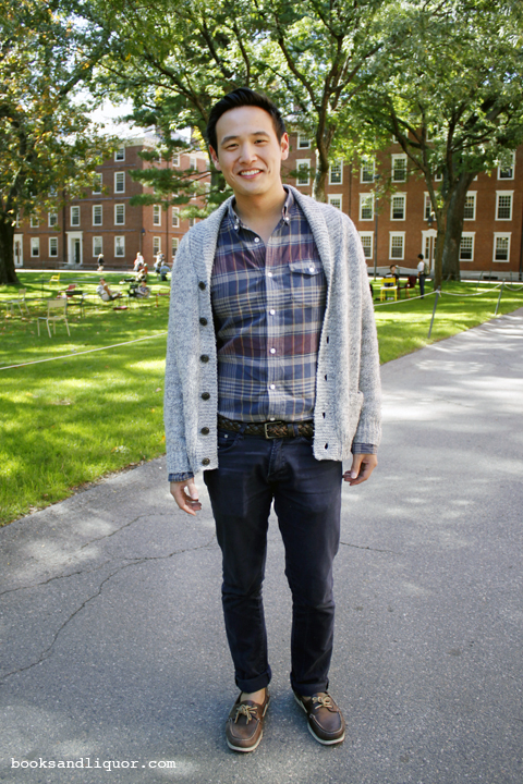 Harvard University student wearing a plaid shirt under a gray wool cardigan and over blue jeans with a woven brown leather belt. He is wearing brown boat shoes